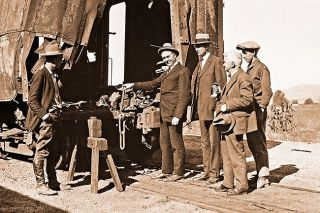 Image: Smithsonian Institute##Unidentified officials pose with the wreckage of the mail car blown up by the DeAutremont Brothers in a bungled attempt to rob it on Oct. 11, 1923.