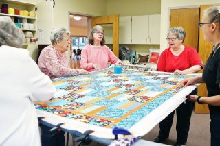 Rockne Roll/News-Register##From left, Janice Logan, Elaine Mitchell, Beth Murphy, Becky Souders and Marsha Restorff assemble the layers of a quilt on a frame at the McMinnville Senior Center.