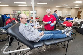 "Marcus Larson/News-Register##Retired teacher Tim Duerfeldt practices a foreign language to pass the time while giving blood Thursday at the Dayton Fire Station. It was Duerfeldt's 172nd donation since 1963. His O-negative blood is considered universal — a quality that makes it especially valuable. ""The need is great; the rewards are high,"" he said. ""Please give blood."""