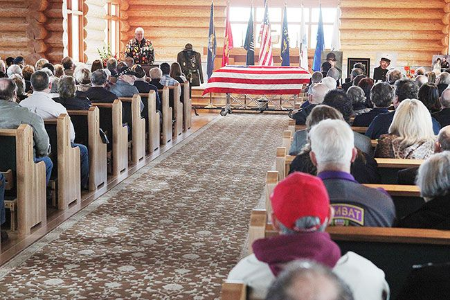 Rockne Roll/News-Register##Ken Buckles, top left, addresses a standing-room-only crowd during a funeral service for Gunnery Sgt. Percy Brandon at Evergreen Chapel in McMinnville on Wednesday, Jan. 20