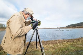 Marcus Larson/News-Register##Harry Fuller peers through a spotting scope for a closer look at a large group of birds resting at Baskett Slough. He suggests new birdwatchers use binoculars with at least 8x40 power.