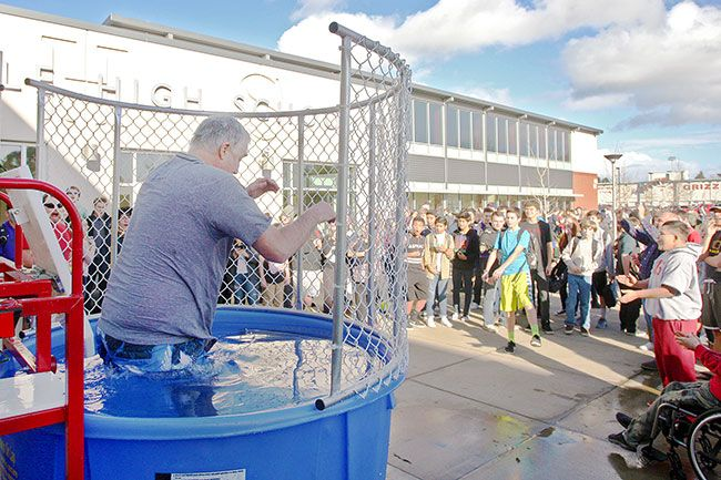 Rockne Roll/News-Register##McMinnville High School teacher Joe Crafton, left, slides into the dunk tank after a successful toss from freshman Nalen Stephens in front of the school Thursday, Jan. 28. The school placed a dunk tank in front of the building during lunch and after classes this week to celebrate the end of final exams.