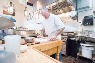 Marcus Larson/News-Register##Danny Wilser said he loves working in his new bakery's kitchen, which glistens with stainless steel. The open space also makes it easy for him to chat with customers while he's working.