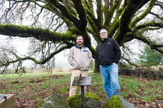 Marcus Larson/News-Register##Doug Root, right, and distiller Kyle LeClerc, under the oak tree marking early settler Ewing Young's burial site. Along with Root's wife, Bev, they are establishing the Ewing Young Distillery and tasting room on the property.