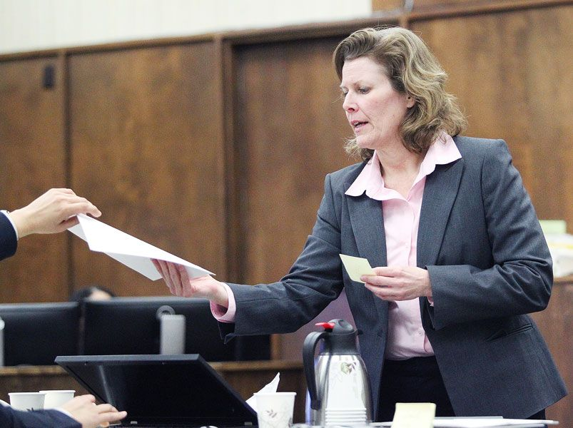 Rockne Roll/News-Register##Prosecutor Kristin Hoffmeyer distributes copies of evidence during Jeremy Hopper II's trial for manslaughter at the Yamhill County Courthouse last Wednesday.