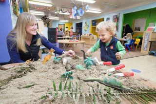 Marcus Larson/News-Register##Parent volunteer Jacque Lambert enjoys playtime with student Elliot Seaton at the McMinnville Cooperative Playschool, housed in the community center. In keeping with the day's paleontology theme, tools sized for small hands were provided so children could excavate plastic dinosaurs and other objects from the sand.