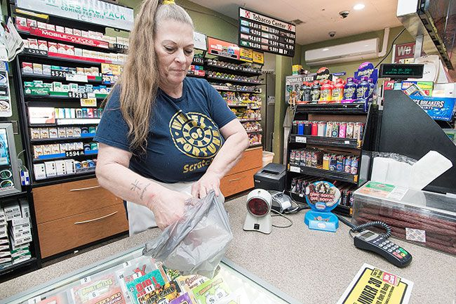 Marcus Larson/News-Register##Patty Keeling, employee of the Circle K on Hill Road, places purchased items in a plastic bag for convenience. The store will soon be required to do away with their plastic bags, a change owner Sunny Singh is concerned about.