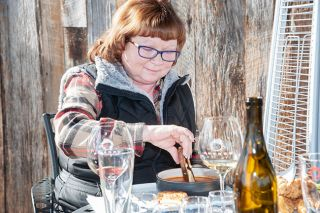 Rusty Rae/News-Register##Jeri Harris of McMinnville dips her Melt Down grilled cheese sandwich into tomato bisque prepared by Brooks Wines chef Norma Buchholz.