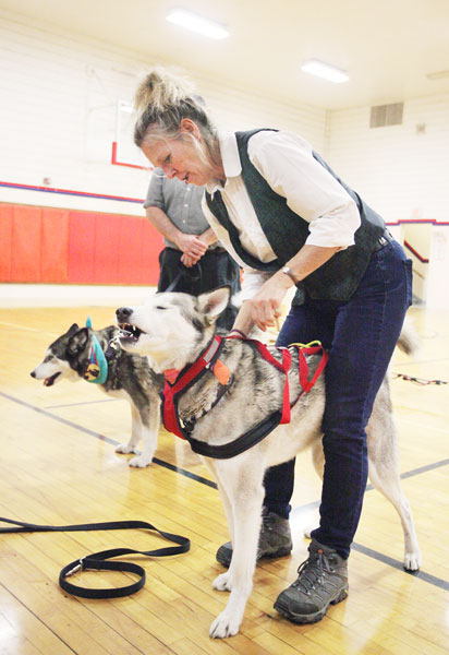 Rockne Roll/News-Register##Lorraine Temple applies a sledding harness to her dog Willow during a presentation to Amity Middle School students Tuesday, Feb. 16.