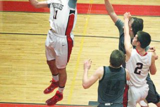 Rockne Roll/News-RegisterMcMinnville's Tanner Autencio (11) grabs a rebound while Walter Stahl (2) boxes out a West Salem player.