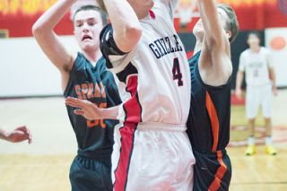 Marcus Larson/News-Register##McMinnville senior guard Cameron Fox (4) puts up a shot between two Sprague defenders in the Grizzlies' 49-47 victory over the Olympians Tuesday night at The Furnace. Fox scored one point in the contest, his first appearance of the season.