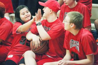 Rockne Roll/News-Register##Jessica Solis, left, high-fives David Knuts during McMinnville High School's Unified Sports basketball game against Forest Grove at The Furnace on Feb. 17.