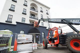 Marcus Larson / News-Register##Using a techhandler, construction workers lift new furniture up to the second floor of the Atticus Hotel. The boutique hotel is scheduled to open April 1, along with BYH Burgers on the ground floor, which is hosting a burger party and job fair Sunday.