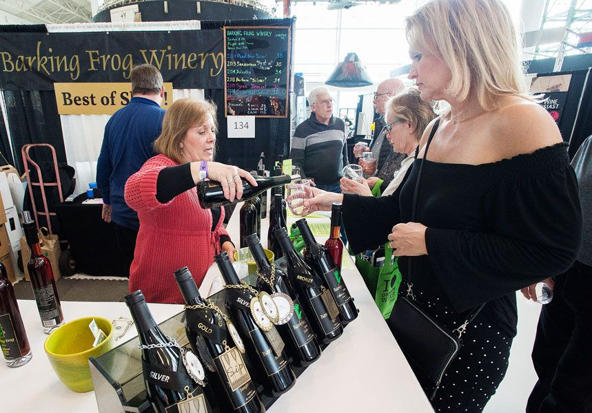 Marcus Larson / News-Register## Cindy Helbig of the Barking Frog winery pours a selection of their 2014 Pinot Noir for patron Diana Treichel during the SIP event at Evergreen Aviation. Barking Frog won top honors in the 2018 Sip awards competition.
