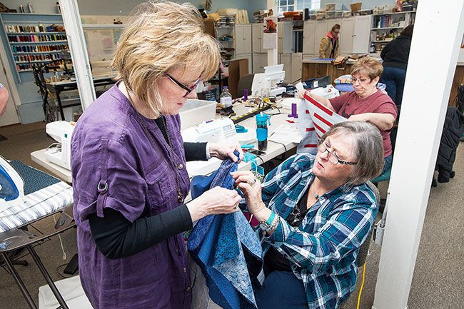 Marcus Larson/News-Register##Jane Petersen and Marlene Thomas discuss how to change the length of a piece of fabric as they finish a quilt top. They and other volunteers gather on Fridays to make Quilts for Cops.