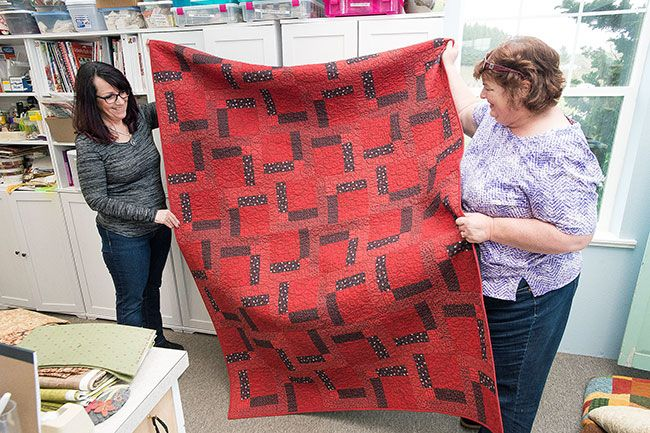 Marcus Larson/News-Register##Hope Sprunger and Bobbie Abernathy-Bebereia hold up a finished quilt that will go to a recently injured firefighter. The nonprofit provides comfort quilts for any first responder.