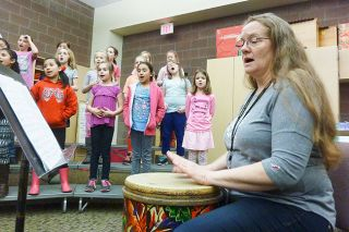 Starla Pointer/News-Register##Robin Pederson taps out the beat as Newby Elementary's after school choir rehearses an African number. She said she often chooses African tunes to teach students about musical rhythm.