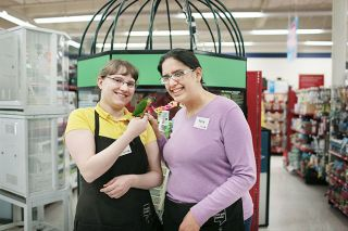 Submitted photo##MV Advancements client Rene Dominic, right, poses with her coworker Leah Baker and Lilly the bird at the McMinnville Petco store.