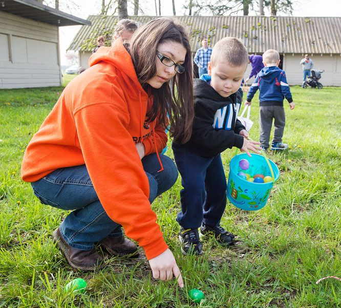 Marcus Larson/News-Register##Sierra Hofmann leads her cousin Alekzander Gallegos to another egg as she helps out with Yamhill s annual Easter Egg hunt. The Homesteaders 4-H Club hosted the event Saturday.