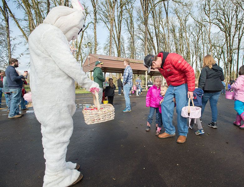 Marcus Larson/News-Register##Ross Dumdi tries to get his two daughters, Olivia and Stella, to say hello to the Easter Bunny. A little intimidted by the large rabbit, the younger girl, Stella, gripes her father tightly.