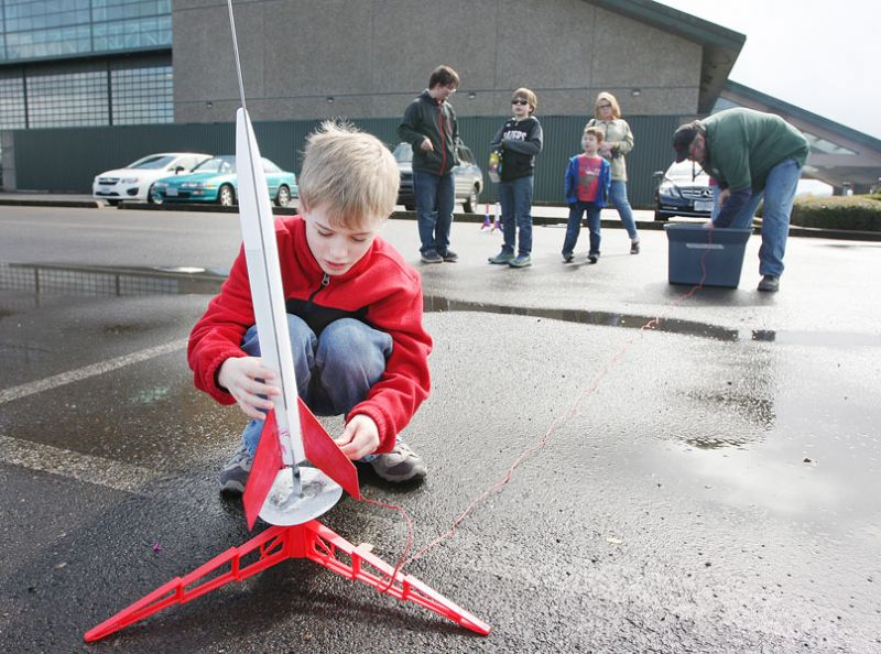 Rockne Roll/News-Register##Jake Green prepares his model rocket for liftoff. The Evergreen camp introduced kids to concepts in engineering, physics and mathematics, as well as reinforcing the importance of teamwork and safety.
