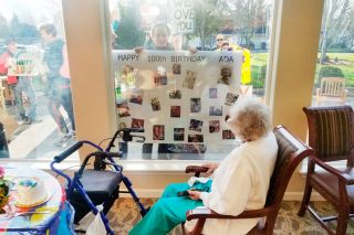Submitted photo##Great-granddaughter Whitney Rich holds photos of Ada Rich up to the window during a social distancing birthday party March 31 at Vineyard Heights in McMinnville. Ada's son and daughter, grandchildren and great-grandkids gathered outside to celebrate the family matriarch's centennial.