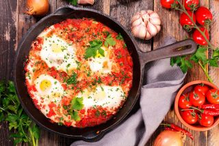 Can Stock Photo##Eggs cooked in spicy tomato sauce are delicious served with garlic bread.