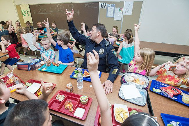 Marcus Larson/News-Register##Yamhill-Carlton second graders and Police Chief Kevin Martinez hold up their hands, signaling it's time to become quiet. They had been chatting happily about police and school activities.