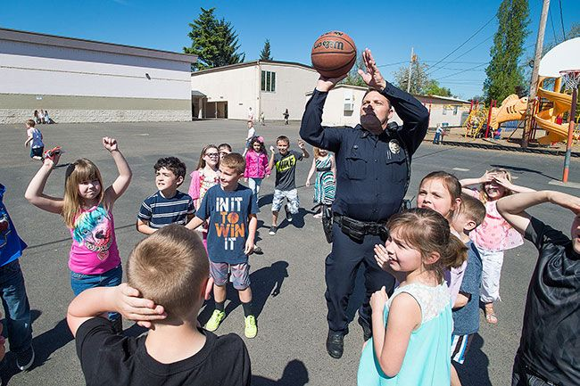 Marcus Larson/News-Register##Carlton Police Chief Kevin Martinez plays basketball with students during his visit to Yamhill-Carlton Elementary School. Martinez and Officer Jake Blair had lunch at the school, then played with kids on Thursday.