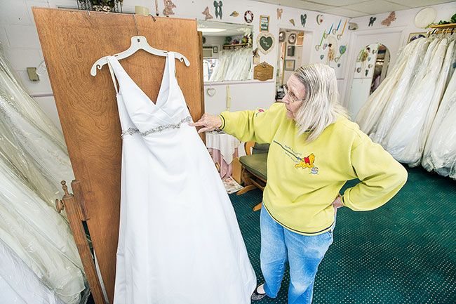 Marcus Larson/News-Register ## Juanita Layton points out sparkling embellishments on one of the formal bridal gowns in her shop.