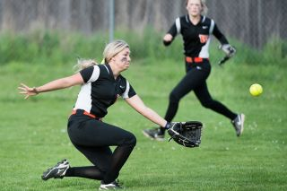 Marcus Larson/News-Register##Willamina left fielder Nikia Mooney (foreground) goes into a slide to catch a fly ball against Sheridan. Mooney successfully made the catch and threw out a runner at first base on the play.