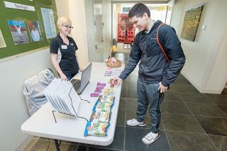 Marcus Larson/News-Register##Chemeketa student Aldrich Yanez grabs a quick snack bar from the STORM Table, staffed by Jamie Corff. Corff and other students run the table, which offers a changing array of items to help with studies.