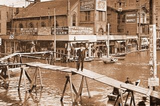 Image: Portland City Archives##Nattily dressed Portland businessmen carry on during the 1894 flood, using a makeshift bridge to cross flooded Third Street at the intersection with Washington Street.