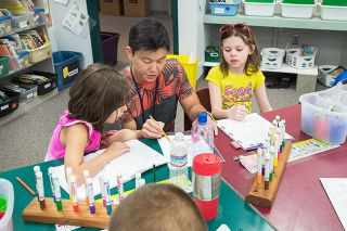Marcus Larson/News-Register##Columbus second-grade teacher Reid Kimura helps students Alyse Waldron and Sarah Leggett with their literacy work.