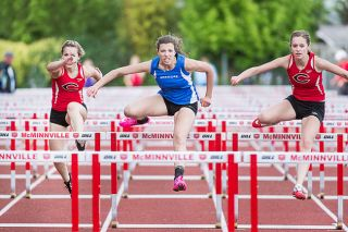 Amy Kraemer of Amity (center) set a personal record of 16.28 seconds in winning the girls' 100-meter hurdles race at the McMinnville Invitational, held Friday at Wortman Stadium.