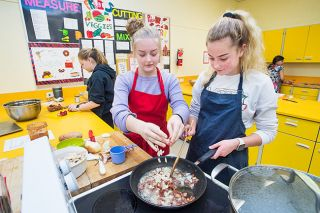 Marcus Larson / News-Register##In kitchen five, Maddie Brown adds onions to the frying pan as Jayden Marshall stirs.