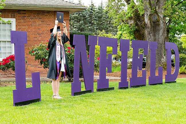 Marcus Larson/News-Register ## Graduate Amanda Reser poses for a portrait with the traditional Linfield letters after receiving her diploma.