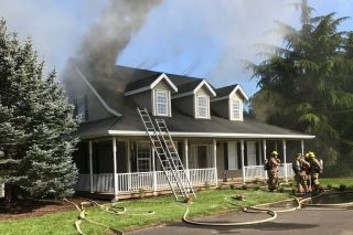Tualatin Valley Fire & Rescue photo##Smoke pours from the rural Newberg home Monday afternoon.