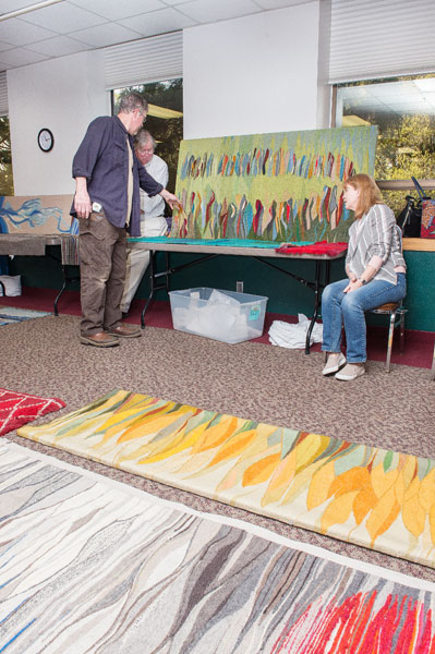 Rusty Rae/News-Register ##  The Johansens display their mother's tapestries in the McMinnville Community Center so weaving guild members can plan a show. Everyone was drawn to the Native myth piece on the far wall.