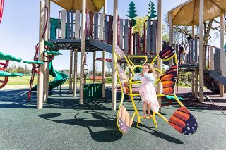 "Marcus Larson/News-Register##Faye Westendorf, 4 1/2, tries out the butterfly ladder at the new Wennerberg Park playground, which also features slides, a bridge and other areas meant to appeal to youngsters. ""It's good!"" Faye said. Grants paid for the play equipment."