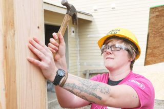 Rockne Roll/News-Register##Liz Hart drives a nail outside what will be the garage of a Habitat for Humanity house Wednesday during their Women Build Project.