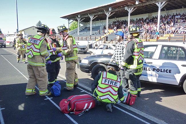 Starla Pointer / News-Register##As community members and students watch from the grandstand, medics assist a  victim  of the mock crash Friday morning.