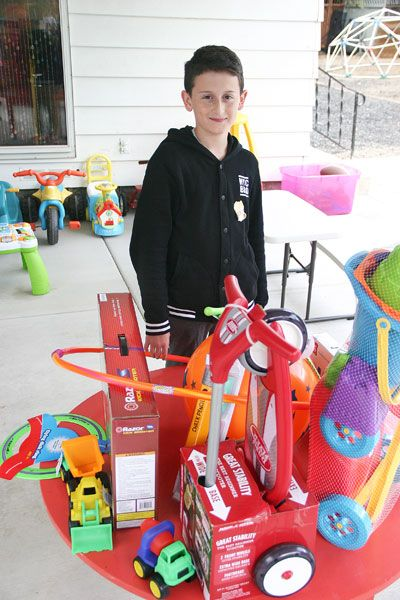 Tom Henderson/News-Register##Christopher Dillworth, 11, spent half his money from Lemonade Day May 2 to buy toys for the new play area at Henderson House. Members of McMinnville's