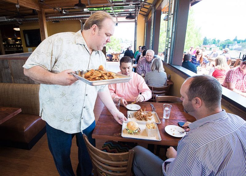 Marcus Larson/News-Register##Owner of the newly opened 1882 Grille, Dustin Wyant, helps serve food to