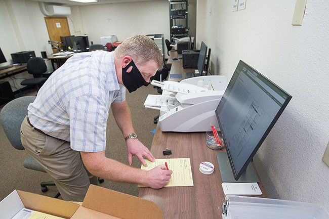 Marcus Larson/News-Register##Yamhill County Clerk Brian Van Bergen fills out a form confirming the voting machine is working properly during a pre-election test last week.