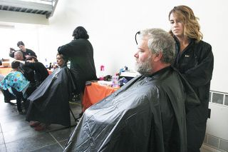 Rockne Roll/News-Register##Tim Simonson, left, was one of many event participants to get a haircut courtesy of Northwest College of Beauty students like Morgan Lundgren.