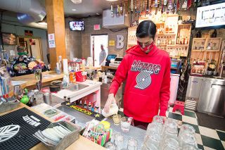 Marcus Larson/News-Register##By-Pass Bar and Grill bartender Isaiah Benavidez mixes a drink for a customer.  Owner Mylee Smith, left, was recently able to rehire Benavidez after she received her PPP loan.