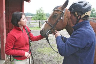Rockne Roll/News-Register##Client Dharam Friedberg and Aztec Max get reacquainted Tuesday as Justin Leahy of Foothills Farms adjusts the horse's bridle. Willamette Coast Ride, Justin