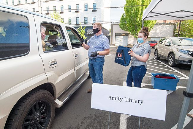 Marcus Larson/News-Register##Yamhill County Clerk Brian Van Bergen and volunteer Sara Price go through the procedure for collecting ballots with other volunteers that travel to each ballot box.