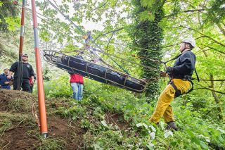 Marcus Larson/News-Register##Jay Payne with McMinnville Fire Department uses an elaborate rope-and-pulley system to demonstrate a mountain rescue with volunteer Brook Fisher.